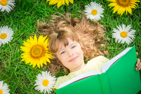 child-reading-book-in-park